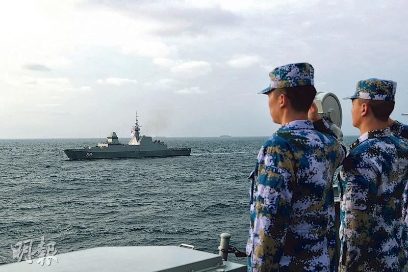 解放軍近期頻演習,讓台灣政情中人解讀為消耗台軍戰力。圖為2月24日,解放軍與新加坡海軍的海上聯合演習,新加坡「剛毅」號導彈護衛艦(左)從解放軍驅逐艦旁駛過。(新華社)