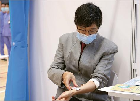 繼去年全民自願檢測自行採集鼻咽及咽喉拭子樣本後,港大微生物學系講座教授袁國勇昨日到中山紀念公園體育館,為自己接種BioNTech疫苗。他接到疫苗時說:「正啊,睇清楚,make sure無bubble喺度……我自己嚟呀。」他在手臂注射後,針口附近輕微腫起,「起咗個波喺度」,「我呢個皮裏注射好痛㗎!」他打針後見傳媒解釋,皮裏注射痛過肌肉注射,一般只需肌肉注射,他以較痛方式注射都「頂得順」,盼藉此呼籲市民勿因怕痛而拒絕接種疫苗。(袁國勇提供)
