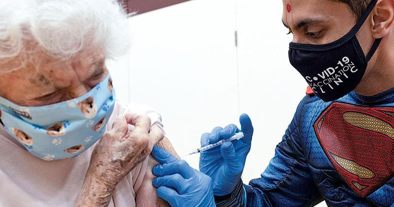 美國賓夕法尼亞州有診所一名醫生周日打扮成超人,為一名94歲老婦注射BioNTech-輝瑞新冠疫苗。(路透社)