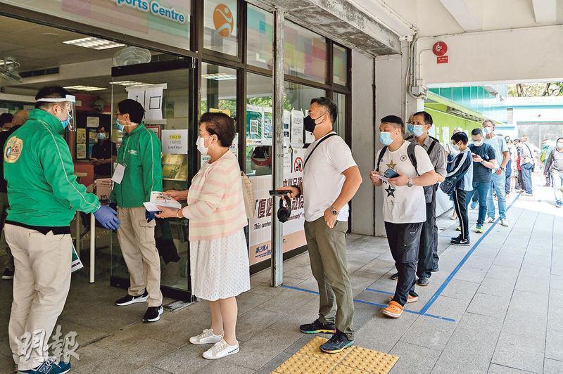 提供BioNTech疫苗的觀塘曉光街體育館接種中心門外現人龍,昨午約2時許約有20名市民排隊等候,部分為非華裔。(林靄怡攝)