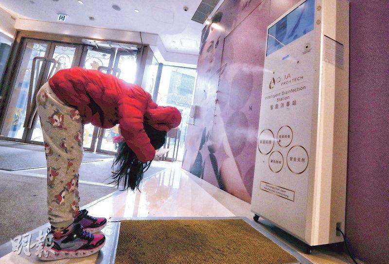 消委會提醒,坊間智能消毒站噴嘴位置有可能直接噴向小童面部,應多加留神。圖為北角匯AQUA PRO+TECH消毒站,一名小童正彎腰「洗頭」。(李紹昌攝)