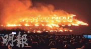 韓國濟州在新型冠狀病毒大流行下,上周六(13日)舉行一年一度的「野火節」,其間在一處空地以火炬砌出「2019新冠病毒離開」的字樣,現場觀眾只能在汽車內觀賞。(路透社)