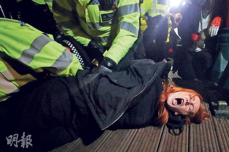 前天在倫部南部的悼念現場,兩名警察把一名女示威者按在地上拘捕,後者狀甚痛苦。(路透社)