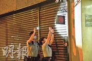 涉事「黃店」門外掛有「追求自由民主」標誌,警員進入餐廳前,以電筒反覆查看該標誌,又拍照記錄。(蔡方山攝)