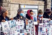 新疆官員透露,新疆部分企業和民眾將起訴德籍學者鄭國恩和英國廣播公司。圖為本月9日有新疆人在中國駐哈薩克阿拉木圖總領館外舉牌示威,抗議其家人被拘押。(法新社)