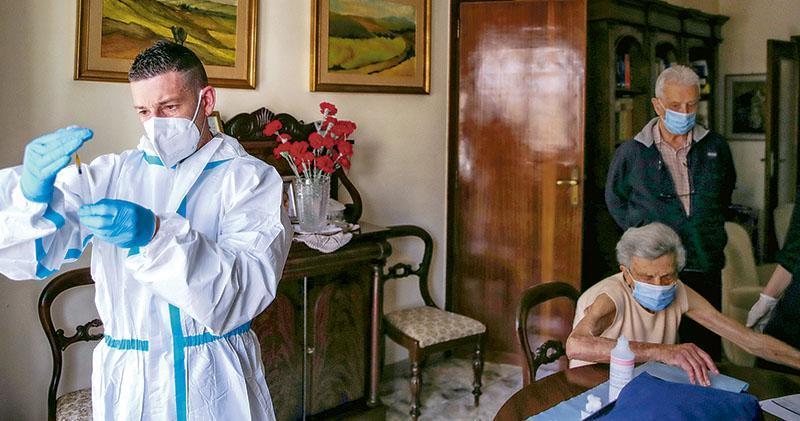 意大利羅馬周三有醫護人員上門,為不方便出門的長者注射BioNTech-輝瑞疫苗。(路透社)