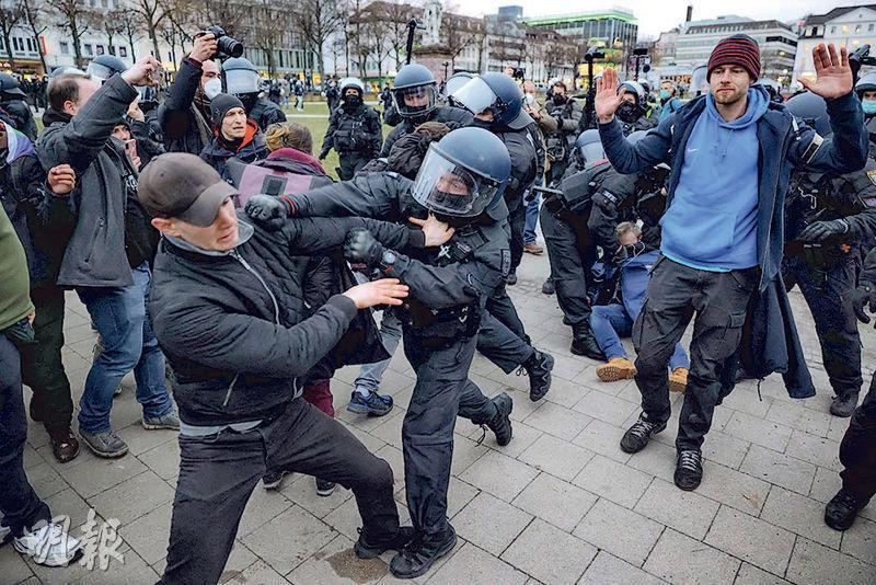 德國卡塞爾市約有兩萬人抗議封城,其間有人想衝出政府規限的示威範圍而與警察爆發衝突,警察動用水炮和胡椒噴霧控制人群。(法新社)