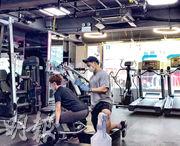 旺角Fitness D2健身室使用天花板嵌入式冷氣,東主郭先生說,政府未就健身室換氣量訂出標準,想改裝通風系統亦無從入手,希望政府提供技術支援。圖為市民昨午在該店教練指導下做舉重訓練,其間兩人均有戴口罩及手套。(劉焌陶攝)