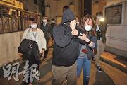 被捕的吳耀漢女兒(前中)昨晚被關員押走,她離開時戴着黑色口罩,並以外套的帽遮着雙眼。(伍浦鋒攝)