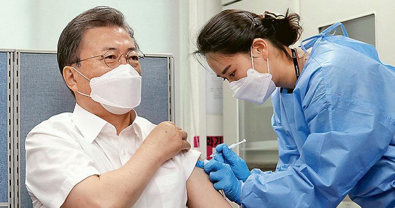 韓國總統文在寅(左)昨在首爾一間衛生中心接種第一劑牛津-阿斯利康疫苗。(法新社)