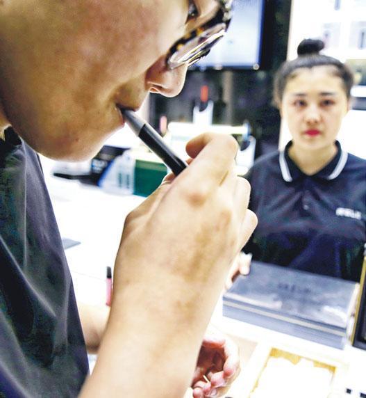 工信部有意將電子煙參照傳統捲煙納入規管,消息引發電子煙板塊昨日「股災」。圖為內地市民於北京試用霧芯科技旗下品牌「悅刻」電子煙。(路透社)