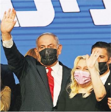 以色列總理內塔尼亞胡(左)昨與妻子在耶路撒冷的利庫德集團黨總部向支持者揮手。(路透社)