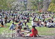 法國巴黎一個公園周三有大批民眾在享受日光浴,同日總統馬克龍宣布法國將於周六起第三度全國封城。(新華社)