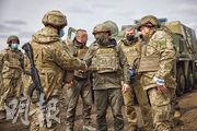 烏克蘭總統澤連斯基(中)周四到東部靠近親俄分離分子陣地的前線政府軍據點慰問軍人。(路透社)