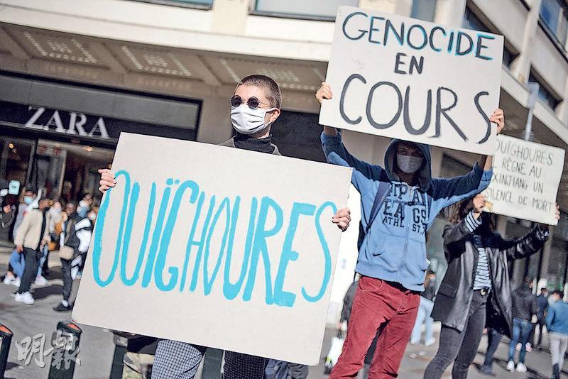 法國數個NGO和一名曾被關押在新疆的維吾爾族女子9日入稟巴黎法院,控告西班牙服裝品牌ZARA母公司Inditex集團等4間跨國服裝企業,從新疆維族人遭強迫勞動中獲利。圖為上月法國一間ZARA門店外有示威者舉牌支持新疆維族人。(法新社)