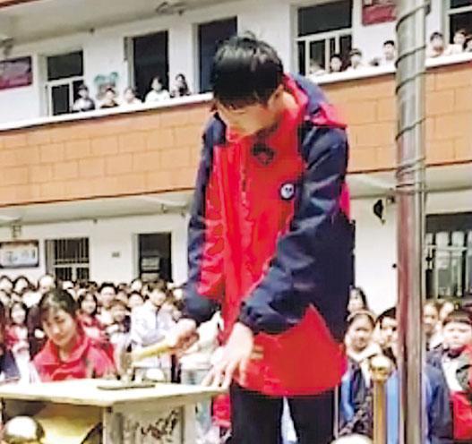 河南一中學讓學生當眾用鐵槌打爛手機,遭輿論批評做法極端,有侵犯學生財產權之嫌,並影響學生價值觀。(網上圖片)