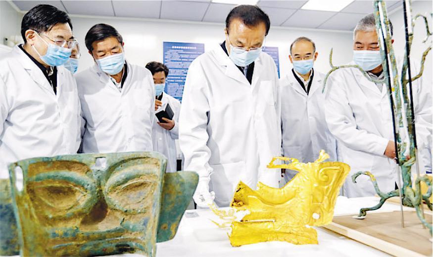 在四川考察的國務院總理李克強,前日到廣漢三星堆考古發掘現場。圖為李克強(右三)戴着口罩、手套拿起出土文物端詳。(網上圖片)