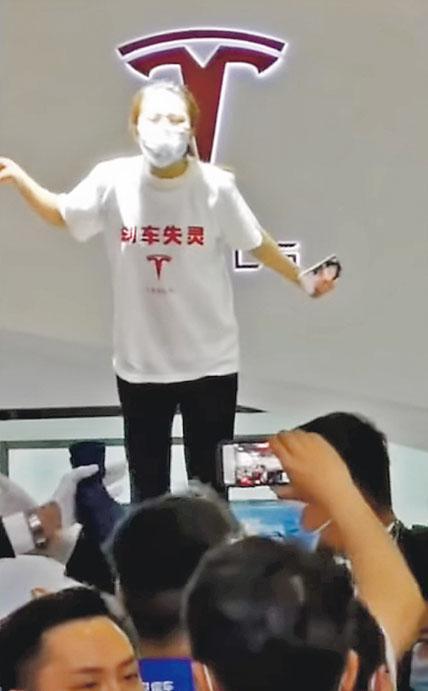 周一(19日)在上海國際車展首日,一名女車主身穿寫着「剎車失靈」字樣的T恤,站在特斯拉展台的車頂抗議。(網上圖片)