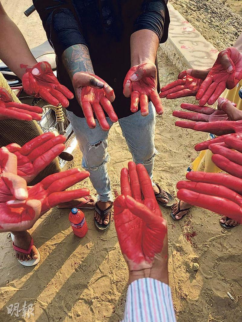 周日有緬甸民眾在facebook上載圖片,顯示曼德勒省城市敏建(Myingyan)有民眾示威抗議軍事政變,示威者的手掌塗成紅色並作出象徵反抗威權獨裁的三指禮。(法新社)