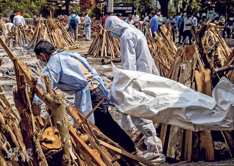 印度新德里周三有民眾把死於新冠病毒肺炎的親友,搬運到火葬場的柴堆上準備火化。(路透社)