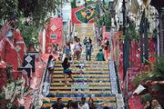 巴西周四(4月29日)成為全球第二個累計死亡人數突破40萬的國家,圖為遊客周四到訪里約熱內盧著名景點「塞勒隆階梯」,但不少人沒戴口罩。(法新社)