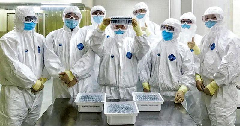 共青團中央、全國青聯昨頒授「中國青年五四獎章」,北京科興中維生物技術有限公司「克冠行動」工作團隊等20個青年集體獲得表彰。圖為科興工作人員在車間展示灌裝好的新型冠狀病毒滅活疫苗。(網上圖片)