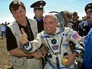 全球首名太空遊客蒂托(中)完成8天太空之旅回地球着陸後,豎起拇指。(法新社)
