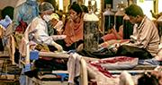 印度新型冠狀病毒疫情持續,單日新增確診個案連日打破紀錄。圖為首都新德里昨日有醫護人員,在一間由宴會廳臨時改建而成的醫療中心照料新冠肺炎患者,當中牀位相當密集。(法新社)