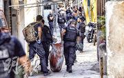巴西里約熱內盧雅卡雷濟紐貧民窟周四一場警匪搏火之後,警察在現場抬走一名受傷疑犯。(路透社)