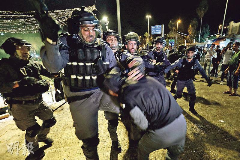 上周六耶路撒冷舊城「大馬士革門」附近,以色列警員與巴勒斯坦示威者扭打。(路透社)