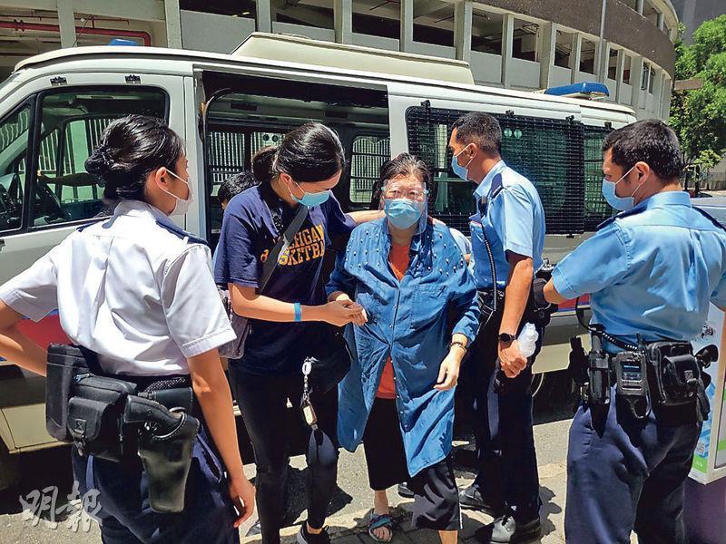 警方陪同打針後不治印傭的僱主(中)返回何文田欣圖軒單位調查。(孫華中攝)