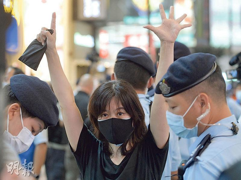 昨日警方持續在銅鑼灣截查市民,一名自稱「香港人」女子稱在場勸喻警方冷靜,被拉入防線截查,其間她舉起「五一」手勢。(鄧宗弘攝)