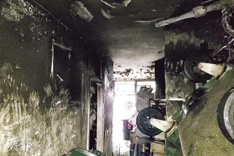 涉事單位牆壁及天花熏黑,廚房放滿雜物。圖中垃圾車為房署職員用作清理單位雜物。(衛永康攝)