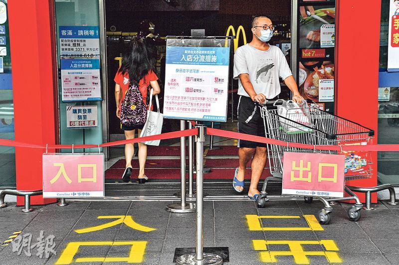 台北市強制實施周末依身分證字號尾數分流採買措施,周日為尾數單數民眾可採買。圖為昨日當地一處賣場在門口貼出告示提醒。(中央社)