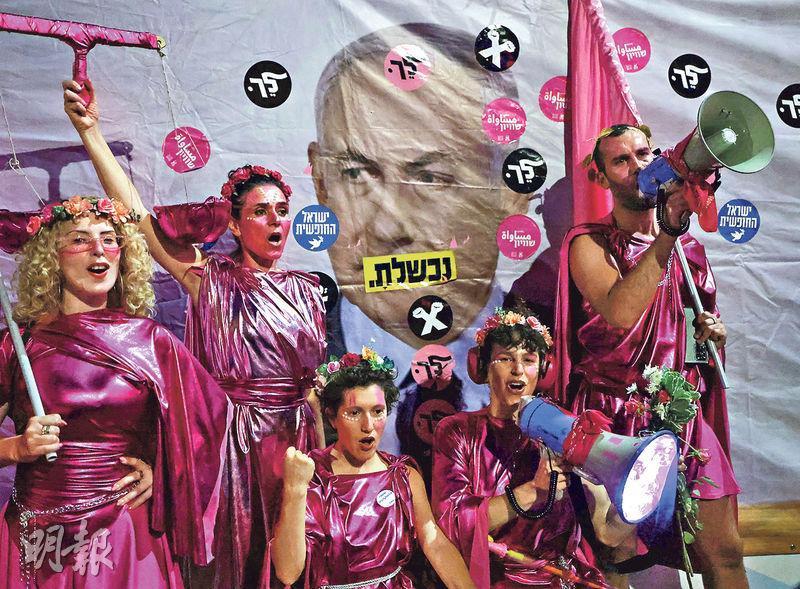 以色列耶路撒冷有示威者上周六到總理內塔尼亞胡的官邸外示威,諷刺他將因涉貪等罪行受審判。以色列國會周日將投票通過組建新政府,內塔尼亞胡的總理生涯亦會結束。(法新社)