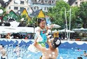 圖為重慶市一個水上樂園昨日開始夏季活動,家長帶小孩浸在泡泡消暑。(中新社)