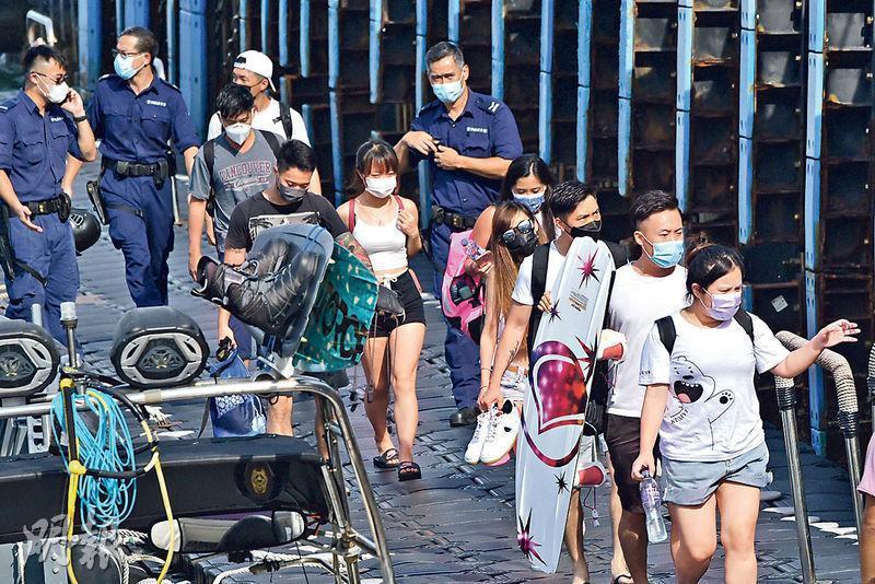 遊艇上約15名同行男女帶同滑水板及個人物件登岸。(衛永康攝)