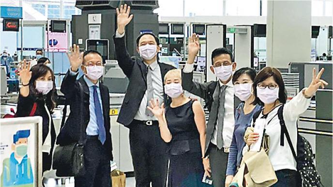 台北經濟文化辦事處7名駐港員工,包括代理處長林振宙(左三)昨日返台,在香港機場揮手道別。陸委會稱他們面對打壓忍辱負重,向他們表達感謝。(陸委會提供)