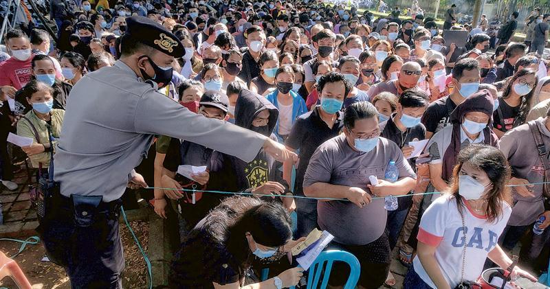 在Delta變種病毒株感染個案湧現的印尼,昨有大批峇里島登巴薩群眾輪候接種新冠疫苗,警員在場維持秩序。(路透社)