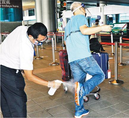 圖為昨日台北桃園國際機場,機場防疫的士司機為入境旅客全身消毒。(中央社)