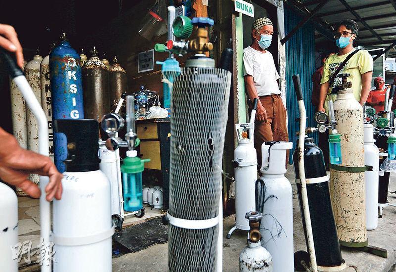印尼雅加達昨有民眾戴着口罩在相關店舖外輪候補充氧氣罐。該國新冠疫情再掀緊張,有消息指衛生部長促請政府收緊控疫措施。(路透社)