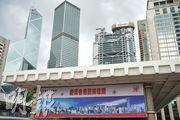 國安法生效一年,金融市場以交投角度看,運作如常;但金融業界稱難獨善其身。金管局去年向銀行業界發出文件,要求本地銀行遇到疑似違反國安法的交易,應即時向警方舉報。警方也數度以國安為由,要求銀行凍結客戶資產。圖為中環金融區,近日多處展示賀香港回歸及共產黨黨慶的宣傳品。(楊柏賢攝)