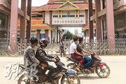 連接緬甸的瑞麗姐告大橋昨起禁止通行,若有特殊情况需要進出姐告,須憑市指揮部發放的通行證出入。圖為昨日,緬方的電單車客駛經中緬邊境已關閉的中國國門。(法新社)