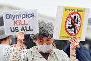 日本東京周五有反對舉辦奧運人士,在火炬傳遞活動場地外舉起標語抗議,左邊的英文標語稱「奧運會殺死我們」。(路透社)