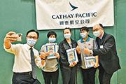 國泰航空職員昨日在國泰城透過外展服務接種BioNTech疫苗,其間公務員事務局長聶德權(左一)與運輸及房屋局長陳帆(右一)到場視察,並與完成接種的員工自拍留念。(政府新聞處)