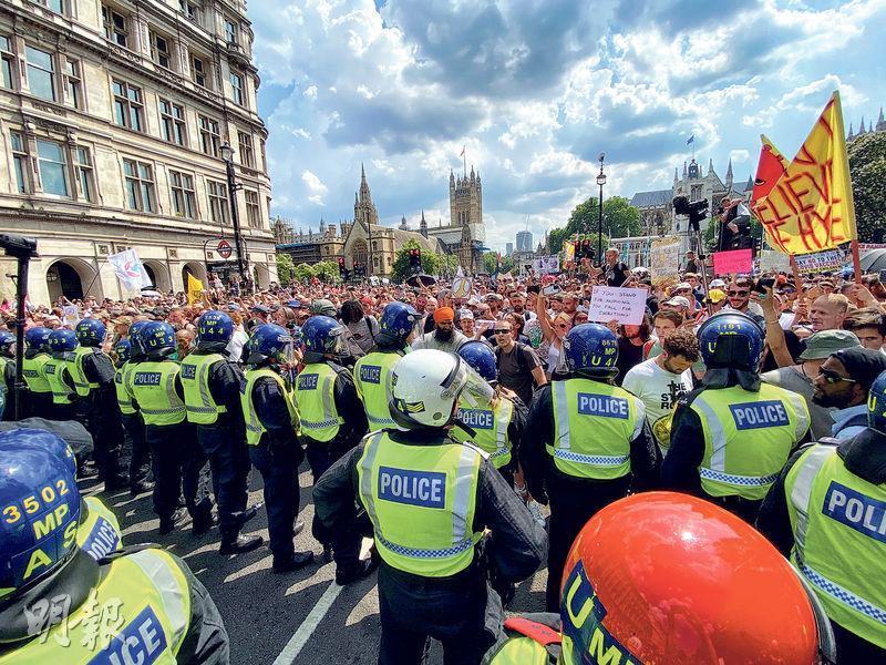 英國周一起解除英格蘭大部分防疫限制,同日有民眾到倫敦國會廣場示威,抗議當局在疫情期間實施的限制,有大批警員在場戒備。(路透社)