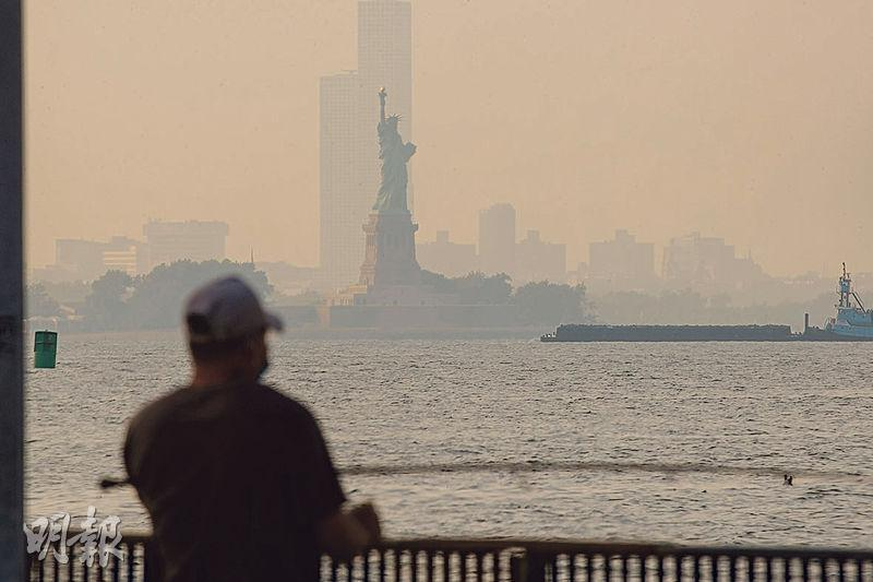 美國紐約周三受山火煙霧影響,自由神像變得模糊。(路透社)