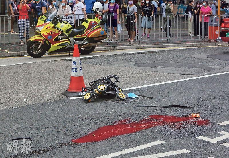 八旬婦於啟田道橫過馬路時遭垃圾車撞倒,警方事後封鎖現場蒐證,路面遺留血漬及損毁的手推車。(伍浦鋒攝)