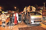 的士翻側後與客貨車高度相若,消防及救護員在車頂為受傷的士乘客初步治理,其後合力將他抬至地面,交由救護車送院。(蔡方山攝)